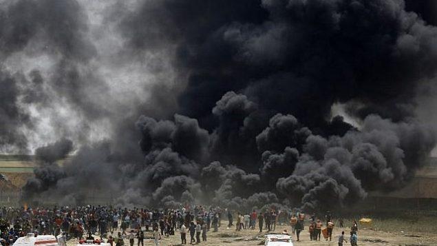 فلسطينيون يحرقون إطارات في السياج الحدودي مع إسرائيل،  شرق جباليا في وسط مدينة غزة، خلال مظاهرة في 13 أبريل، 2018. (AFP PHOTO / MOHAMMED ABED)