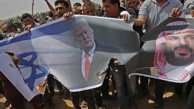 فلسطينيون يستعدون لإشعال النار بعلم إسرائيل وصور للرئيس الأمريكي دونالد ترامب وولي العهد السعودي محمد بن سلمان خلال مظاهرة في السياج الحدودي مع إسرائيل، شرق خان يونس في جنوب مدينة غزة، في 13 أبريل 2018. (AFP PHOTO / Thomas COEX)