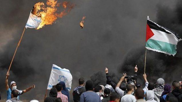 محتجون فلسطينيون يحرقون الأعلام الإسرائيلية بالقرب من السياج الحدودي مع إسرائيل، شرق خان يونس في جنوب مدينة غزة، في 13 أبريل 2018. (AFP/Thomas Coex)