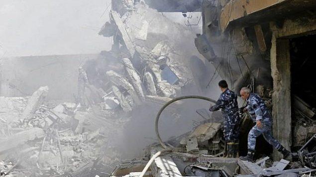 الجنود السوريون يتفقدون حطام مبنى وُصف بأنه جزء من مجمع مركز بحوث جمرايا في منطقة برزة، شمال دمشق، خلال مؤتمر صحفي نظمته وزارة الإعلام السورية، 14 أبريل، 2018.  (AFP / LOUAI BESHARA)