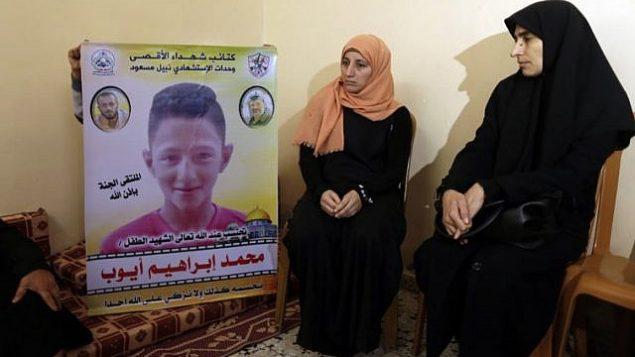 والدة الطفل الفلسطيني (وسط الصورة) البالغ من العمر 15 عاما والذي قُتل بحسب تقارير بنيران الجيش الإسرائيلي خلال مواجهات عند السياج الحدودي بين غزة وإسرائيل، تجلس إلى جانب شخص آخر يرفع صورته، في منزل العائلة في بيت لاهيا في شمال قطاع غزة في 21 أبريل، 2018.  (AFP PHOTO / MAHMUD HAMS).