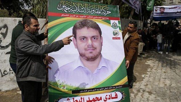 صورة تم التقاطها في 21 أبريل، 2018 تظهر رجالا يرفعون ملصقا يحمل صورة  صورة البروفسور والعضو في حركة حماس، فادي محمد البطش (35 عاما) الذي قُتل في وقت سابق من اليوم في ماليزيا، خارج منزل عائلته في جباليا شمال الضفة الغربية. ( AFP PHOTO / MAHMUD HAMS)