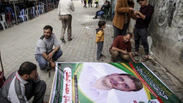 صورة تم التقاطها في 21 أبريل، 2018 تظهر رجالا يعدون ملصقا يحمل صورة البروفسور والعضو في حركة حماس، فادي محمد البطش (35 عاما) الذي قُتل في وقت سابق من اليوم في ماليزيا، خارج منزل عائلته في جباليا شمال الضفة الغربية. ( AFP PHOTO / MAHMUD HAMS)