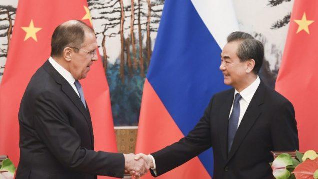 وزير الخارجية الروسي سيرغي لافروف (من اليسار) ونظيره الصيني وانغ يي يتصافحان في نهاية مؤتمر صحفي مشترك في بكين، 23 أبريل، 2018. (AFP PHOTO / POOL / MADOKA IKEGAMI)