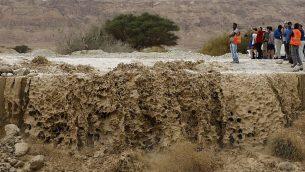 اسرائيليون يراقبون مياه جرف سدت طريق رئيسي بالقرب من البحر الميت، في اعقاب امطار عزيرة في الجبال المحيطة، 25 ابريل 2018 (AFP PHOTO / MENAHEM KAHANA)