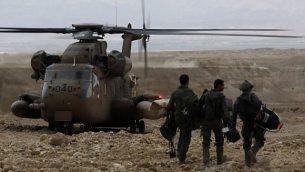 جنود يسيرون نحو طائرة هليكوبتر عسكرية خلال مهمة بحث لعدة شبان مفقودين في جنوب إسرائيل بعد أن اجتاحت الفيضانات المنطقة وهم يمشون بالقرب من البحر الميت في 26 أبريل، 2018. (AFP PHOTO / MENAHEM KAHANA)