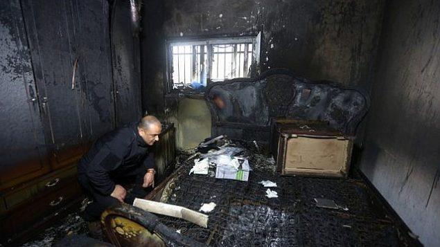 صورة توضيحية: شرطي فلسطيني يتفقد الأضرار داخل منزل محترق في حادثة اضرام نار في العام الماضي قام بها متطرفون يهود أسفرت عن مقتل عائلة فلسطينية، في قرية دوما بالضفة الغربية، في الساعات الأولى من يوم 20 مارس 2016. (AFP / Jaafar Ashtiyeh)