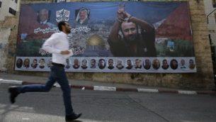فلسطيني يمر من أمام ملصق يحمل صورة للقيادي والأسير الفلسطيني مروان البرغوثي في مدينة رام الله في الضفة الغربية، 3 مايو، 2017.  (AFP/ ABBAS MOMANI)