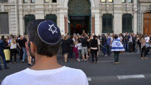 رجل يرتدي قلنسوة، بينما يشارك الناس في مظاهرة دعا إليها مجلس ممثلي المؤسسات اليهودية في فرنسا في 31 يوليو 2014، أمام كنيس ليون. (AFP/Romain LaFabregue)