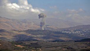 صورة توضيحية: سحب الدخان تتصاعد من قرية الحضر الدرزية السورية في 3 نوفمبر، 2017، كما تظهر من الجانب الإسرائيلي لهضبة الجولان. (AFP/JALAA MAREY)