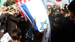 مؤيدو الحكومة الإيرانية يحرقون الأعلام الإسرائيلية والأمريكية خلال مسيرة في مشهد لدعم النظام بعد أن أعلنت السلطات نهاية الاحتجاجات الأخيرة، في 4 يناير  2018. (AFP Photo/Tasnim News/Nima Najafzadeh)