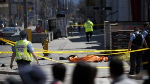 TORONTO, ON - APRIL 23: A tarp lays on top of a body on Yonge St. at Finch Ave. after a van plowed into pedestrians on April 23, 2018 in Toronto, Canada. A suspect is in custody after a white van collided with multiple pedestrians.   Cole Burston/Getty Images/AFP