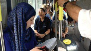 طالبة فلسطينية تقرأ كتبها المدرسية على متن القطار الخفيف في شعفاط، القدس، 20 سبتمبر 2014 (Elhanan Miller / Times of Israel)