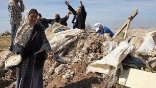توضيحية: فلسطينيون يحاولون استخراج أغراضهم من حطام منزل بعد قيام جرافات الجيش الإسرائيلية بتدميره بالقرب من قرية سوسيا في الضفة الغربية في عام 2011. (Najeh Hashlamoun/Flash90)