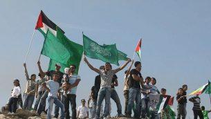 فلسطينيون يلوحون بأعلام حماس وهم يحتفلون باتفاق تبادل الأسرى الذي تم التوصل إليه بين إسرائيل وحماس في القدس الشرقية 18 أكتوبر 2011. (Kobi Gideon / Flash90)