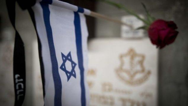 عشية ذكرى ضحايا حروب إسرائيل وضحايا الهجمات، علم تم وضعه على قبور جنود في المقبرة العسكرية في جبل هرتسل في القدس، 28 أبريل، 2017. (Yonatan Sindel/Flash90)