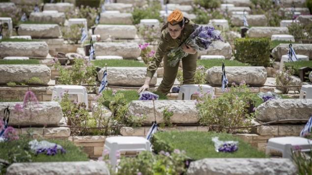 عشية انطلاق فعليات ذكرى ضحايا حروب ومعارك إسرائيل وضحايا الهجمات، جنود إسرائيليون يضعون الزهور على قبور جنود في المقبرة العسكرية في جبل هرتسل في القدس، 30 أبريل، 2017. (Yonatan Sindel/Flash90)