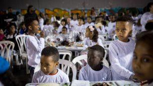 طلاب من مدرسة بياليك ، في جنوب تل أبيب، والعديد منهم أطفال ملتمسي اللجوء الأفارقة، يحضرون عشاء ما قبل عيد الفصح في فناء المدرسة في 20 مارس، 2018. (Miriam Alster / FLASH90)