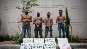 طالبو لجوء أفارقة في محاكاة لمزاد لبيع العبيد في إطار احتجاج ضد ترحيلهم من أمام وزارة الدفاع في تل أبيب، 3 أبريل، 2018. (Miriam Alster/Flash90)