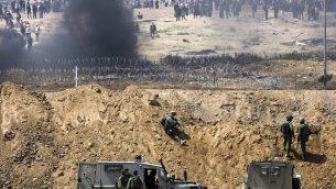 متظاهرون فلسطينيون يحرقون إطارات بالقرب من الحدود مع إسرائيل في قطاع غزة، كما يظهرون من الطرف الإسرائيلي من الحدود، 13 أبريل، 2018.  (Sliman Khader/Flash90)