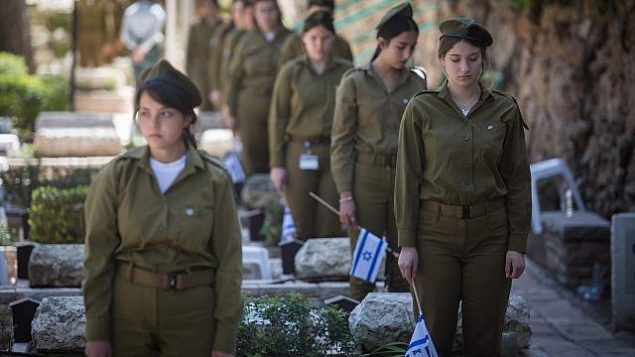 جنديات إسرائيليات يضعن الأعلام على قبور جنود في المقبرة العسكرية في جبل هرتسل في مدينة القدس، 16 أبريل، 2018 قبل انطلاق فعاليات إحياء يوم الذكرى لضحايا حروب ومعارك إسرائيل.  (Hadas Parush/Flash90)