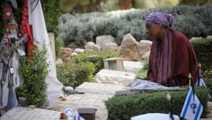 إسرائيليون يجلسون بجانب قبور أعزائم خلال المراسم الرسمية لإحياء ذكرى ضحايا حروب ومعارك إسرائيل وضحايا الهجمات في جبل هرتسل في القدس، 8 أبريل، 2018. (Miriam Alster/Flash90)
