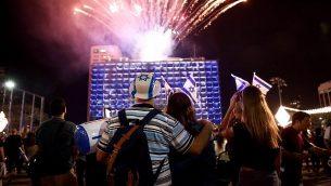 اشخاص يشاهدون الالعاب النارية خلال الاحتفال بيوم استقلال اسرائيل في تل ابيب، 18 ابريل 2018 (Miriam Alster/Flash90)