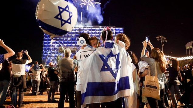 أشخاص يشاهدون غرض الألعاب النارية احتفالا بيوم استقلال إسرائيل ال70 في تل أبيب، 18  أبريل، 2018. (Miriam Alster/Flash90)