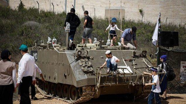 إسرائيليون يحتفلون بيوم الإستقلال في معرض للجيش الإسرائيلي في مستوطنة إفرات في عوض عتصيون، 19 أبريل، 2018. (Gershon Elinson/Flash90)