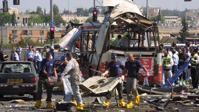 مسعفون وعناصر الشرطة في ساحة عملية انتحارية فلسطينية راح ضحيتها 19 شخصا واثيب فيها 74 على متن حافةل في القدس، 18 يونيو 2002 (Flash90/File)