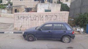 سيارة تم تمزيق اطاراتها امام حائط تم تخريبه بعبارة باللغة العبرية في قرية دير عمار الفلسطينية في الضفة الغربية، 25 ابريل 2018 (Yesh Din)