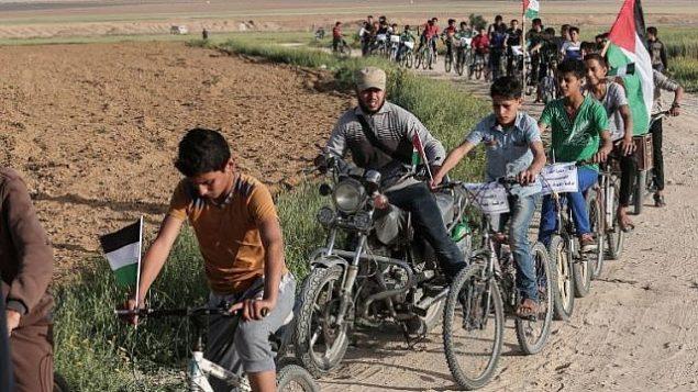 أطفال فلسطينيون يركبون الدراجات بالقرب من الحدود مع إسرائيل في ضواحي مدينة خان يونس في جنوب قطاع غزة، خلال مشاركتهم في سباق دراجات للمطالبة ب'حق العودة' لملايين الفلسطينيين إلى إسرائيل، 26 مارس، 2018. (AFP/Said Khatib)