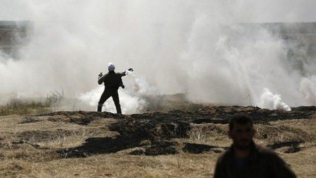 رجل فلسطيني يلقي قنبلة غاز مسيل للدموع بخلال اشتباكات عند الحدود بين غزة واسرائيل، 6 ابريل 2018 (MAHMUD HAMS / AFP)