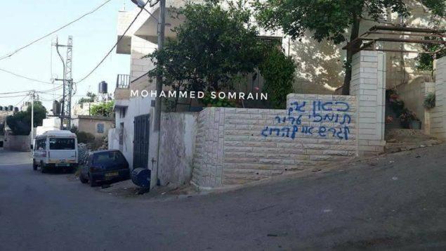 عبارة 'هنا يسكن داعمي ارهاب. الترحيل او القتل'، مكتوبة على جدران قرية برقة الفلسطينية في الضفة الغربية، 20 ابريل 2018 (Mohammed Somrain)