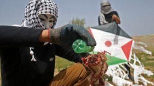 فلسطينيون عند الضواحي الشرقية لمدينة غزة يحضرون زجاجة حارقة لربطها بطائرة ورقية وتطييرها فوق السياج الحدودي مع إسرائيل، 20 أبريل، 2018.  (AFP Photo/Mohammed Abed)