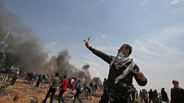متظاهر  فلسطيني  يستخدم   مقلاعا لإلقاء الحجارة على الجنود الإسرائيليين بالقرب من مدينة خان يونس، في جنوب قطا ع غزة، خلال يوم الجمعة الخامس على التوالي من المظاهرات الحاشدة والمواجهات عند الحدو بين غزة وإسرائيل في 27 أبريل، 2018.  (AFP Photo/Said Khatib)