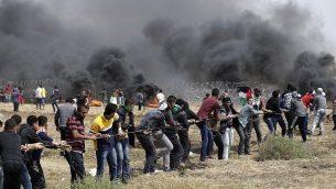 فلسطينيون يحاولون إسقاط جزء من السياج الحدودي بين إسرائيل وغزة شرق جباليا في شمال قطاع غزة، خلال خامس يوم على التوالي من التظاهرات على طول الحدود بين غزة وإسرائيل، في 27 أبريل، 2018. (AFP Photo/Mahmud Hams)