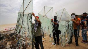 فلسطينيون يعدون طائرة ورقية قبل محاولة تطييرها مع مواد حارقة فوق السياج الحدودي مع إسرائيل، في خان يونس جنوبي قطاع غزة، 4 مايو، 2018. ( AFP PHOTO / SAID KHATIB)