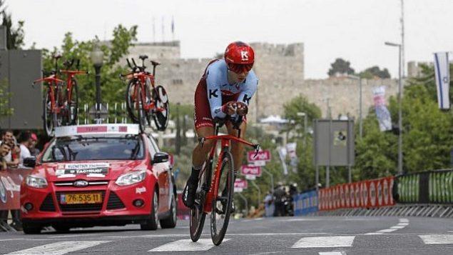 راكب الفريق الروسي كاتوشا، ألبسين فياتسلاف كوزنتسوف، يركب دراجته بالقرب من أسوار مدينة القدس القديمة خلال المرحلة الأولى من سباق غيرو دي إيطاليا  في إيطاليا في 4 مايو 2018، في القدس.(AFP/Menahem Kahana)