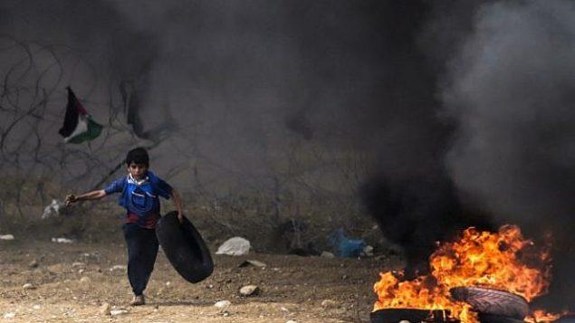متظاهر فلسطيني يركض وهو يحمل إطاراً لإطلاق النار أثناء الاشتباكات مع القوات الإسرائيلية على طول الشريط الحدودي مع قطاع غزة شرق مدينة غزة في 4 أيار / مايو 2018. (AFP PHOTO / MAHMUD HAMS)