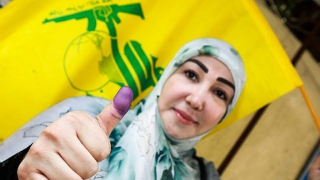 امراة شيعية لبنانية تعرض ابهامها الملون بالحبر وتلوح بعلم حزب الله بعد التصويت في محطة اقتراع في العاصمة بيروت في 6 مايو، 2018، في اليوم الذي تجري فيه البلاد انتخابات برلمانية لأول مرة منذ تسع سنوات. (AFP PHOTO / ANWAR AMRO)