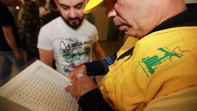 مندوب عن منظمة حزب الله يتحقق من قائمة  الناخبين في محطة اقتراع في الضواحي الجنوبية لبيروت في 6 مايو، 2018،  في اليوم الذي تجري فيه البلاد انتخابات برلمانية لأول مرة منذ تسع سنوات.(AFP PHOTO / ANWAR AMRO)
