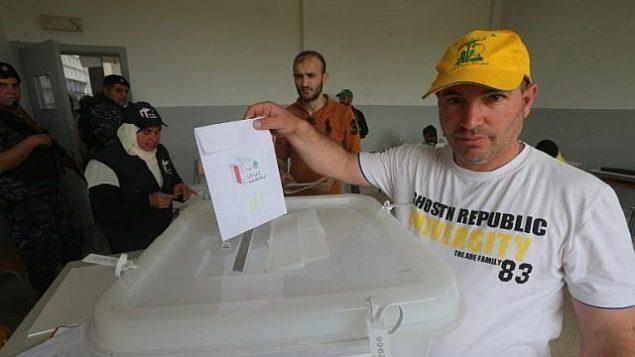 أحد مؤيدي منظمة حزب الله اللبنانية يدلي بصوته في أول  انتخابات برلمانية لبنانية تجرى منذ تسع سنوات، في محطة اقتراع في مدينة بعلبك ذات الأغلبية الشيعية، في وادي البقاع في شرق لبنان بالقرب من الحدود مع سوريا، 6 مايو، 2018. (AFP PHOTO / Haitham MOUSSAWI)
