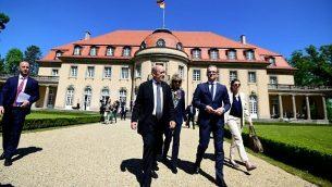 """وزير الخارجية هايكو ماس (من اليمين) ونظيره الفرنسي جان إيف لودريان يسيران خارج دار الضيافة """"فيلا بورسيغ"""" التابعة لوزارة الخارجية الألمانية خلال لقاء لمناقشة شؤؤن متعلقة بالاتحاد الأوروبي وسياسات الدفاع المشتركة وقضايا دولية في 7 مايو، 2018، في برلين. (AFP/Tobias SCHWARZ)"""