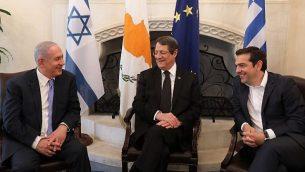 الرئيس القبرصي نيكوس أناستيادسن وسط الصورة، ورئيس الوزراء بينيامين نتنياهو، من اليسار، ورئيس الوزراء اليوناني ألكسيس تسيبراس، يتحدثون خلال لقاء جمعهم في القصر الرئاسي في نيقوسيا، 8 مايو، 2018. (YIANNIS KOURTOGLOU/AFP)