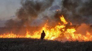 يحاول رجال الإطفاء الإسرائيليون إخماد حريق في حقل قمح بالقرب من كيبوتس ناحال عوز، على طول الحدود مع قطاع غزة، في 8 مايو 2018 بعد أن تسببت فيه الطائرات الورقية التي يرسلها متظاهرون فلسطينيون عبر الحدود. (AFP/Menahem Kahana)