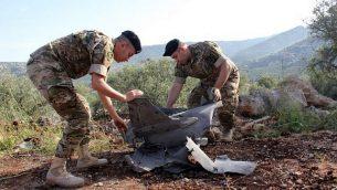 جنود لبنانيون يتفقدون حطام صاروخ أرض-جو سوري تم إطلاقه كما يبدو باتجاه طائرة إسرائيلية خلال غارات مكثفة ضد أهداف إيرانية في سوريا، سقط في قرية الهبارية في جنوب لبنان، 10 مايو، 2018. (Ali Dia/AFP)