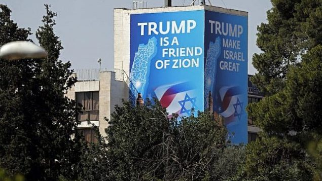 """ملصق يشيد بالرئيس الأمريكي دونالد ترامب يغطي قسما خارجية من """"فندق ديبلومات""""، بالقرب من القنصلية الأمريكية في القدس التي ستكون مقرا للسفارة الأمريكية، 11 مايو، 2018. ( AFP PHOTO / THOMAS COEX)"""