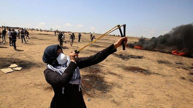 متظاهرة  تستخدم مقلاعا لإلقاء الحجارة أثناء الاشتباكات مع القوات الإسرائيلية على طول الحدود مع قطاع غزة شرق خان يونس في 11 مايو 2018. (AFP PHOTO / SAID KHATIB)