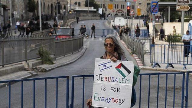 امرأة تحمل لافتة عند باب العامود قبل احتفاليات 'يوم القدس' في ذكرى توحيد المدينة خلال حرب 1967، 13 مايو 2018 (Ahmad GHARABLI/AFP)